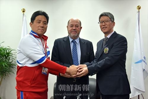 手を取り合う在日本朝鮮人空手道協会の宋修日理事長、世界空手道連盟のアントニオ・エスピノス会長、アジア空手道連盟の王旭輝事務局長(左から)
