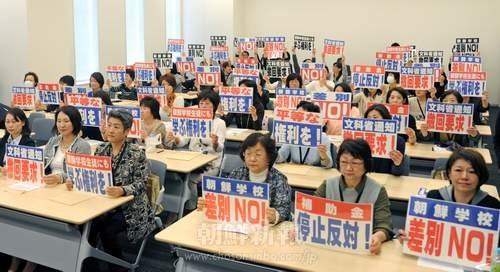 参加者たちはメッセージカードを掲げて抗議の意を示した。
