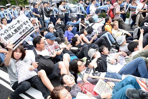 シットインでデモの進路を塞ぐカウンターの市民たち