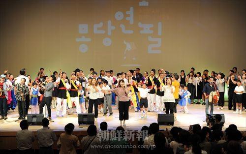 舞台に上がり、踊り、歌う参加者たち