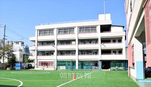 創立70周年記念事業の一環として外壁塗装された校舎と、人工芝を敷いた運動場