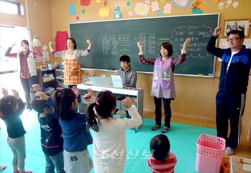 노래에 맞추어 함께 춤추는 어린이들과 강사들