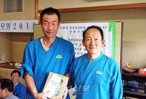 총련본부 조일연위원장(오른쪽)이 와라비분회 김대현분회장에게 기념품을 전달하였다.